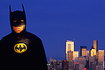 Man dressed as Batman standing beside Seattle Skyline at Twilight