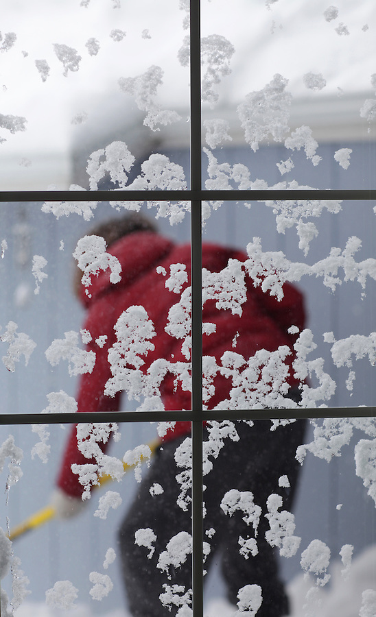A woman in a red winter coat shovels snow, seen through a window covered with patches of snow.