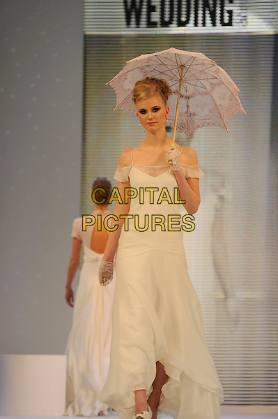 Bride .The National Wedding Show, Olympia, London, England..23rd February 2013 .runway full length model umbrella gloves white dress .CAP/IA.©Ian Allis/Capital Pictures.