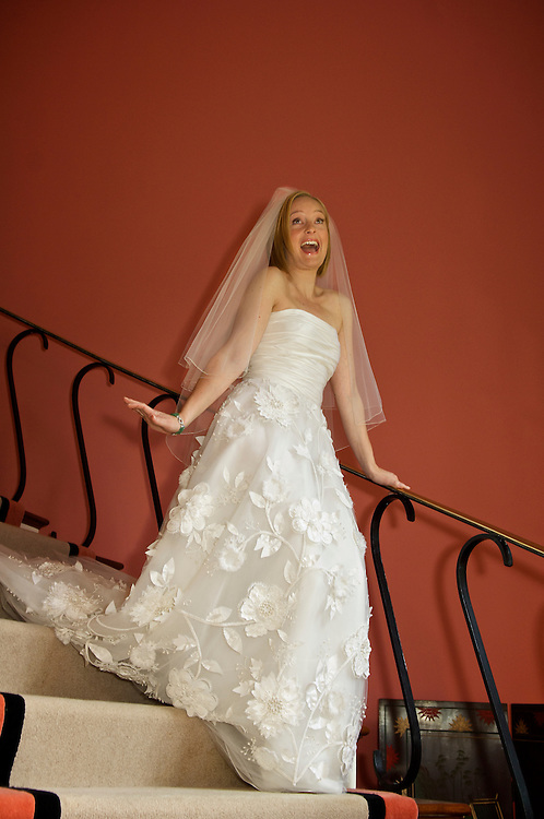 An excited bride in lace dress descending staircase.