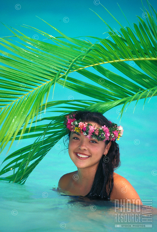 A beautiful, smiling Polynesian woman wearing a haku lei swims in turquoise water with palm fronds above her.