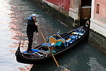 A gondolier in Venice, Italy steers his gondola.