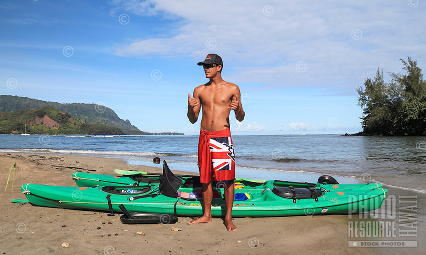 A kayak guide makes shaka signs at Hanalei Beach, Kaua'i.