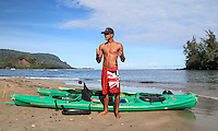 A kayak guide makes shaka signs at Hanalei Beach, Kaua'i.