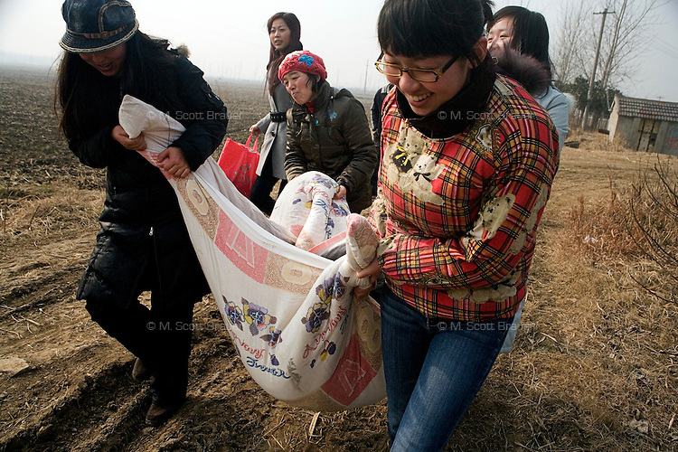 Volunteers carry food, blankets, and other necessities for the dogs and cats at Ha Wenjin's no-kill dog and cat rescue farm outside Nanjing, Jiangsu, China.