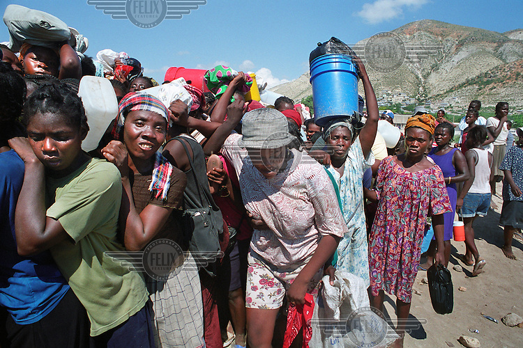 Women queuing for food and relief supplies in the wake of the flood. Food distribution remains difficult, with some aid supplies having been stolen by gangsters..Three weeks after tropical storm Jeanne hit Gonaives parts of the city are still flooded. Over 2700 people were reported dead or missing. Haiti is particularly vulnerable to flooding after heavy rainfall due to intense deforestation.