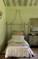 A single four poster bed flanked with a restored chest of drawers