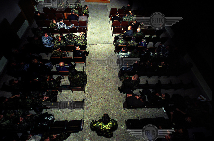 Terek Cossack militiamen, many veterans of the Afghan and Chechen wars, gather for a secret meeting in an underground hall.