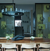 A pair of large sliding doors constructed from etched glass separates the dining room from the kitchen