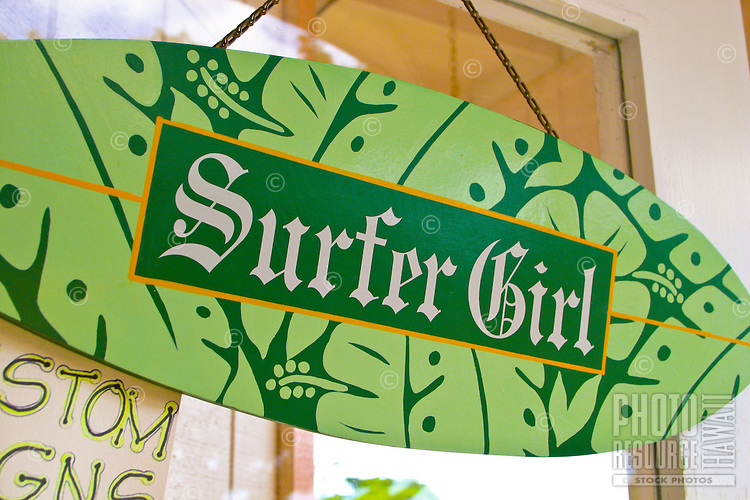 A Surfer Girl surfboard sign hangs as an indication of equality of women within the surfing community. This sign seen outside a northshore gift shop.