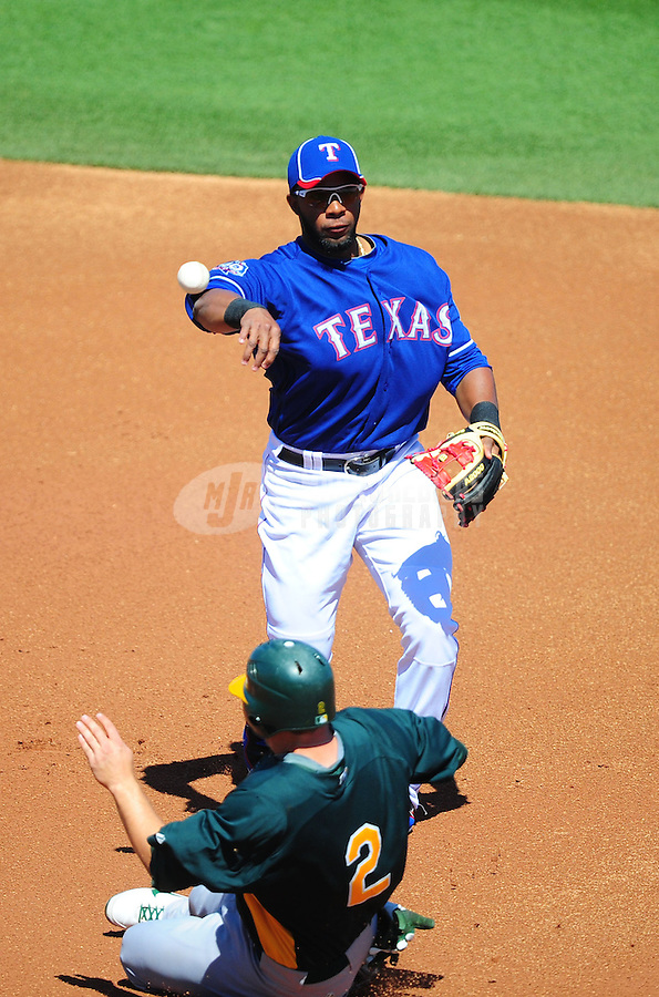Mar. 15, 2012; Surprise, AZ, USA; Texas Rangers shortstop Elvis Andrus throws to first base to complete the double play after forcing out Oakland Athletics base runner Cliff Pennington in the first inning at Surprise Stadium.  Mandatory Credit: Mark J. Rebilas-