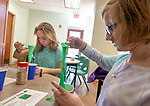 MIDDLEBURY,  CT-031219JS03- Madison Ferguson, 12, left, and Katherine Dean, 11, both from Middlebury, mix together ingredients during a shamrock slime making workshop Tuesday at the MIddlebury Public Library. The slime is made with a mixture of glue, liquid starch, water and food coloring. <br />  Jim Shannon Republican American