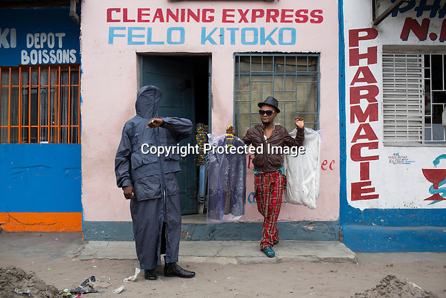 """KINSHASA, DEMOCRATIC REPUBLIC OF CONGO - OCTOBER 3: Mzee Kindingu (r), the leader of the Sapeurs group The Leopards picks up some clothes from a drycleaner on February 3, 2015 in Kinshasa, DRC. The word Sapeur comes from SAPE, a French acronym for Société des Ambianceurs et Persons Élégants. or Society of Revellers and Elegant People. and it also means, .to dress with elegance and style"""". Most of the young Sapeurs are unemployed, poor and live in harsh conditions in Kinshasa, a city of about 10 million people. For many of them being a Sapeur means they can escape their daily struggles and dress like fashionable Europeans. Many hustle to build up their expensive collections. Most Sapeurs could never afford to visit Paris, and usually relatives send or bring clothes back to Kinshasa. (Photo by Per-Anders Pettersson)"""