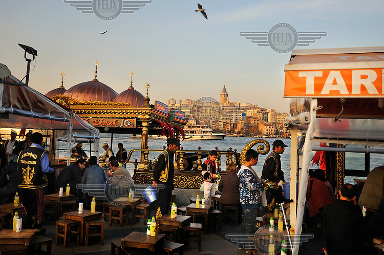Fish sandwich cafe by the Golden Horn with Galata across the waterbeyond. The tables are on the shore, the fish grilled on ornately decorated boats.