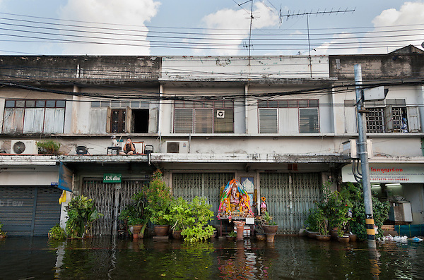 A woman and her dog sit on her balcony taking photos of the flood in western Bangkok.<br /> <br /> Thailand's worst floods for 50 years finally reached the suburbs of Bangkok in October 2011. While the government dithered and argued with itself, more than 200 people died.