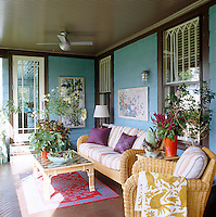 The wrap-around porch of this Victorian shingled weekend house in New Jersey is furnished with wicker seating and colourful textiles