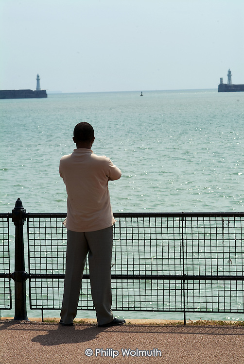 A refugee from Zimbabwe stares out to sea from the promenade near a Dover hotel used by Migrant Helpline to house asylum-seekers awaiting decisions on their asylum applications.