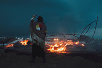 """Dawn Of A New Day prays as a wigwam burns on the eve of an Army Corp of Engineers eviction notice at the DAPL resistance camps near Cannon Ball, ND on Tuesday, February 21, 2016. The owner said, """"it was made in ceremony and it will end that way. I'm not letting it get bulldozed."""""""
