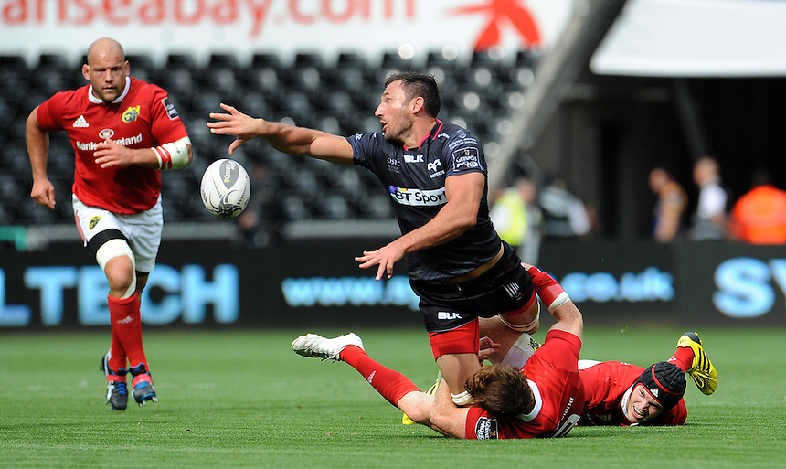 Ospreys' Joe Bearman manages to offload while being tackled by Munster's Cathal Sheridan<br /> <br /> Photographer Ian Cook/CameraSport<br /> <br /> Rugby Union - Guinness PRO12 - Ospreys v Munster - Sunday 13th September 2015 - Liberty Stadium - Swansea<br /> <br /> &copy; CameraSport - 43 Linden Ave. Countesthorpe. Leicester. England. LE8 5PG - Tel: +44 (0) 116 277 4147 - admin@camerasport.com - www.camerasport.com