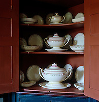 Detail of a full porcelain dinner service displayed in a painted corner cupboard in the dining room