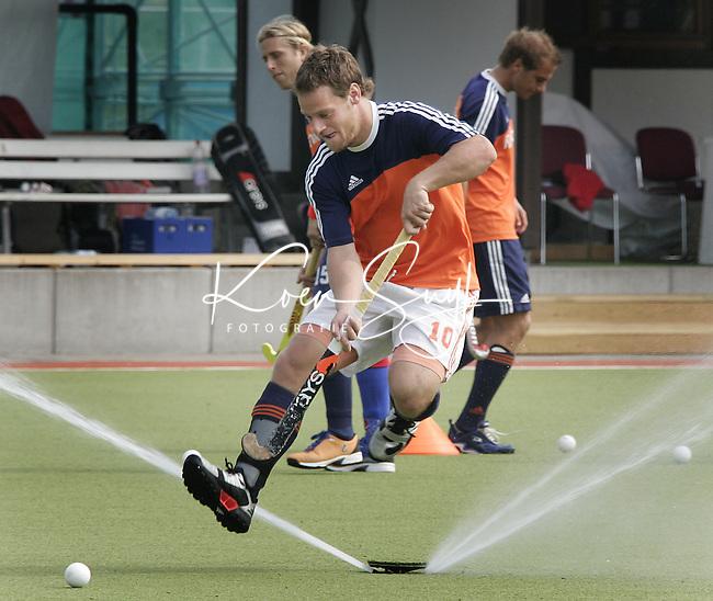 NLD-20050902-Leipzig-EK HOCKEY : De hockeyselectie trainde vrijdag voor de halve finalewedstrijd van zaterdag tegen Belgie. Taeke Taekema ontwijkt een veldsproeier. Op de achtergrond Roderick Weusthof en Sander van der Weide.