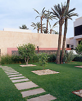 The landscaped garden is geometric in pattern planted with native date palms and a lush lawn