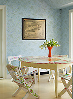 The dining room is decorated in blue pattern wallpaper and the table and chairs are painted with hearts and flowers in the style of folk artist Peter Hunt.