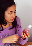 15 year old girl reading directions on liquid medicine container label