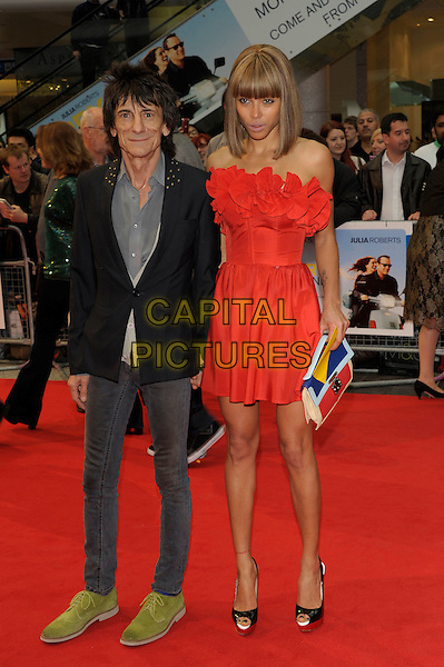 Ronnie Wood, Ana Araujo.'Larry Crowne' world film premiere, Vue cinema, Westfield, Shepherds Bush, London, England 6th June 2011.full length strapless red dress couple grey gray skinny jeans blazer jacket green suede shoes shirt holding hands .CAP/PL.©Phil Loftus/Capital Pictures.