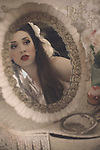 A reflection of a beautiful young brunette woman with long hair looking questioningly into a beautiful vintage mirror on a vanity table