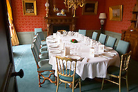 The luxurious classic old-fashioned dining room set for a gala dinner with starched napkins and white table cloth and many glasses for tasting the champagnes as seen through the entrance door at Champagne Deutz in Ay, Vallee de la Marne, Champagne, Marne, Ardennes, France, low light grainy grain