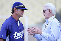 Los Angeles Dodgers manager Don Mattingly #8 talks with former Dodgers general manager Fred Claire before a game against the San Diego Padres at Dodger Stadium on August 30, 2011 in Los Angeles,California. Los Angeles defeated San Diego 8-5.(Larry Goren/Four Seam Images)