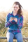 Young adult woman sitting on railing portrait texting