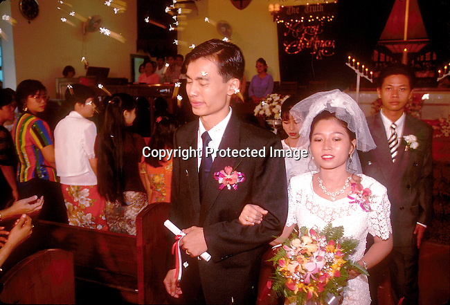 PPWEDDI50014.People. Wedding.  Asian bride and bridegroom standing in front of alter in church.  Candles and benches. Christian.©Per-Anders Pettersson / iAfrika Photos