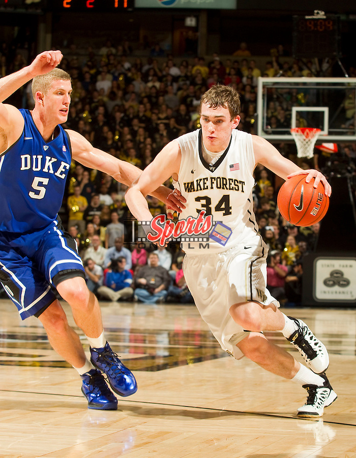 Tyler Cavanaugh (34) of the Wake Forest Demon Deacons drives past Mason Plumlee (5) of the Duke Blue Devils during second half action at the LJVM Coliseum on January 30, 2013 in Winston-Salem, North Carolina.  The Blue Devils defeated the Demon Deacons 75-70.  (Brian Westerholt/Sports On Film)