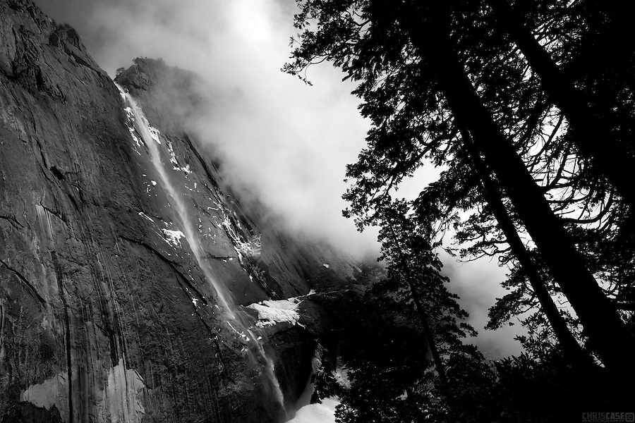 Fog rises from the Yosemite valley to reveal iconic Yosemite Falls, Yosemite National Park, California.