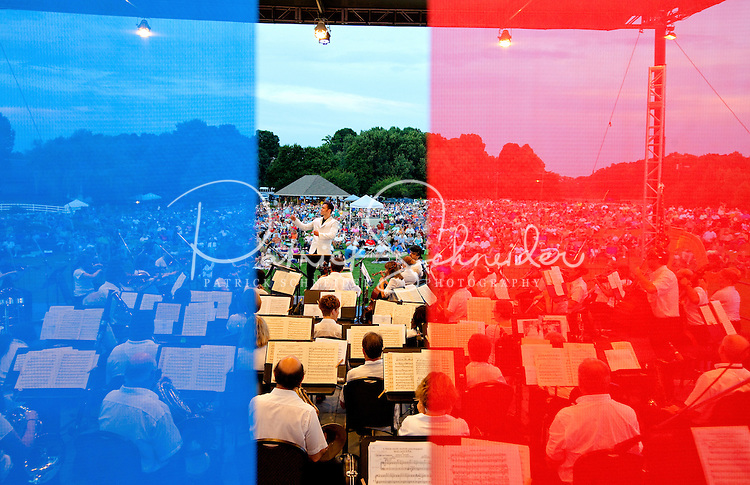 "Event photography of the Charlotte Symphony performing in a free outdoor concert June 17, 2012 at Duke Energy's McGuire Nuclear Station EnergyExplorium in Cornelius, NC. The symphony orchestra performed a ""musical travels"" program. Jacomo Rafael Bairos conducted. Blue and red hues are intentional (photo taken through colored screens on stage)."