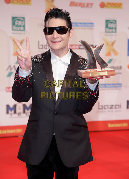 Corey Feldman .Attending the 7thh Kinderlachen Gala 2011, Westfalenhalle, Dortmund, Germany, 26th November 2011..half length black jacket white shirt  sunglasses  diamante crystals sparkly suit tuxedo beige award trophy holding  velvet trousers v peace sign gesture .CAP/PPG/PF.©Patric Fouad/People Picture/Capital Pictures