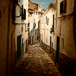 A narrow street in a small town with white houses
