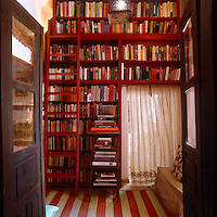 This custom made bookcase covering the entire wall in the library has been painted with the same tone of red as the striped rug