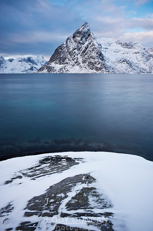 Olstind mountain peak rises from fjord, Lofoten Islands, Norway