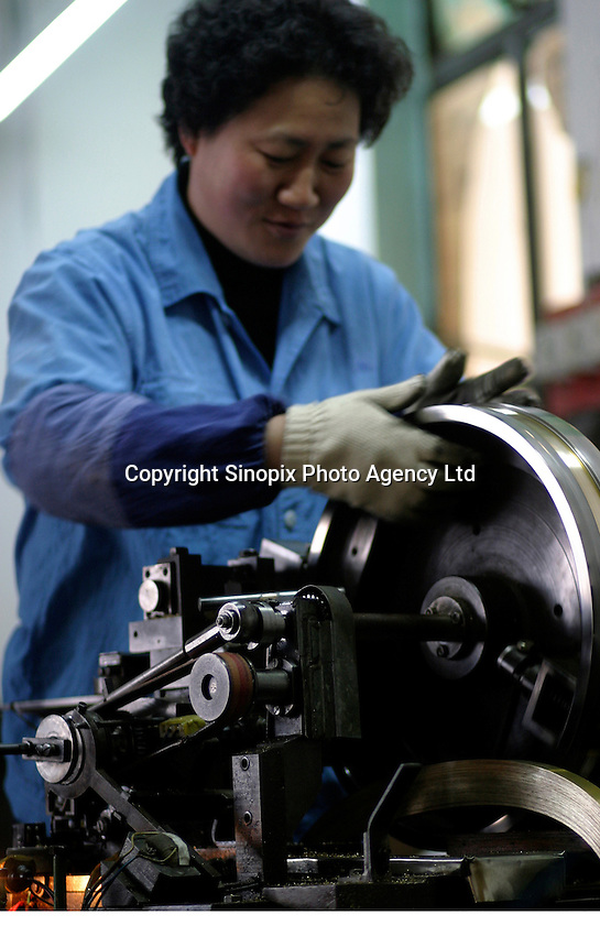A worker operates a machine that smooths down copper strips at the Shanghai General Harmonica Factory (SGHF) in Shanghai, China. Although it makes well-respected brands such as the Huang, Suzuki, and Hohner harmonicas that are favored by many professional musicians around the world, the 60 years old state owned SGHF had to trim down its work force from 800 in the mid 1980's to just over 100 today..23-FEB-04