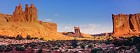 Panoramic of sunrise highlighting 3 Gossips and Courthouse Towers sandstone rock formations in Arches National Park, Utah.