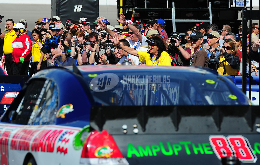 Mar. 5, 2011; Las Vegas, NV, USA; Fans cheer and take pictures as NASCAR Sprint Cup Series driver Dale Earnhardt Jr passes by during practice for the Kobalt Tools 400 at Las Vegas Motor Speedway. Mandatory Credit: Mark J. Rebilas-