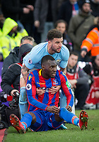 Kyle Walker of Manchester City helps Christian Benteke of Crystal Palace who was sent colliding with the advertising boards after a challenge during the Premier League match between Crystal Palace and Manchester City at Selhurst Park, London, England on 31 December 2017. Photo by Andy Rowland.