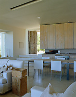 The long dining room table acts aas a boundary between the kitchen area and the rest of the open-plan lving space
