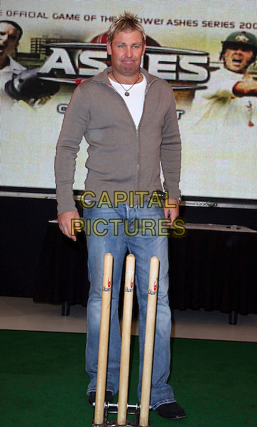 "SHANE WARNE .at the launch of the new ""Ashes"" computer game in central London, England, UK, July 28th 2009..photocall full length jeans brown top grey gray zip up wickets cricket .CAP/DS.©Dudley Smith/Capital Pictures"