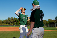 Dartmouth Big Green shortstop Nate Ostmo (5) high fives Steffen Torgersen (29) after a half inning during a game against the Northeastern Huskies on March 3, 2018 at North Charlotte Regional Park in Port Charlotte, Florida.  Northeastern defeated Dartmouth 10-8.  (Mike Janes/Four Seam Images)