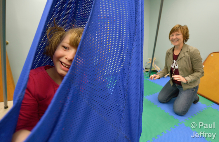 Four-year old Karis Andrews enjoys swinging in the sensory-motor playroom at University United Methodist Church in San Antonio, Texas. The room is part of the congregation's special needs ministries, and is open to the community, providing access to therapeutic toys and equipment at no cost to children with developmental delays. Pushing her is Susan Galindo, the director of disability ministries of the church.