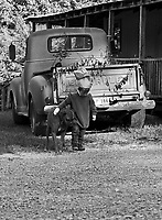 A young boy with a paper bag on his head walks past an old truck, his arm around his dog.